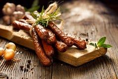 Salchichas en una tabla rústica de madera con la adición de las hierbas y de las especias aromáticas frescas, producto natural de Fotos de archivo