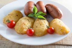 Salchichas fritas y patatas empanadas Imagen de archivo libre de regalías