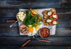 Salchichas grandes del desayuno, brusquets, huevos fritos, queso de la patata y verdes con la salsa Visión superior imagen de archivo libre de regalías