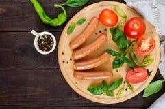 Salchichas jugosas con los tomates y albahaca en una tabla de cortar redonda en un fondo de madera oscuro Fotos de archivo libres de regalías