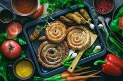Salchichas picantes asadas adornadas con verdes Imagenes de archivo