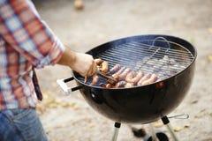 Salchichas que cocinan en una barbacoa Foto de archivo