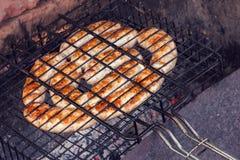 Salchichas que cocinan en una parrilla Imagen de archivo libre de regalías