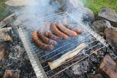 Salchichas que cocinan sobre una parrilla abierta del carbón de leña Fotos de archivo libres de regalías