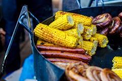 Salchichas recientemente cocinadas en una parrilla con el primer del maíz Backgroun Fotografía de archivo