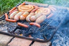 Salchichas sabrosas del cerdo y de la carne de vaca que cocinan sobre los carbones calientes Imagen de archivo libre de regalías