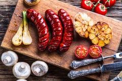 Salchichas Salchichas de la parrilla Salchicha asada a la parrilla con los tomates y las cebollas del ajo de las setas fotografía de archivo libre de regalías