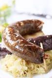Salchichas, sauerkraut y patata cocida al horno Imagen de archivo