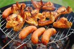 Salchichas y alas de pollo en la parrilla foto de archivo libre de regalías