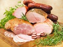 Salchichas y carnes en una tarjeta de corte Imagen de archivo libre de regalías