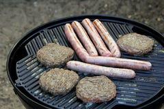 Salchichas y hamburguesas que chisporrotean en una placa de la plancha de la barbacoa Fotografía de archivo