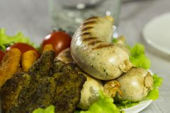 Salchichas y nagets fritos deliciosos de la carne en una placa en las hojas verdes de la lechuga adornadas con los tomates Primer Imagen de archivo libre de regalías