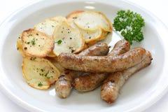 Salchichas y patatas salteadas Foto de archivo