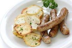 Salchichas y patatas salteadas Imagenes de archivo