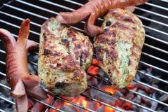 Salchichas y pollo en parrilla de la barbacoa Imagenes de archivo