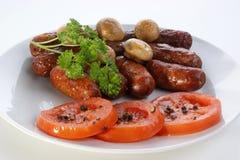 Salchichas y tomate asados a la parilla de la carne de vaca Foto de archivo