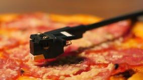 Salchichones de la pizza que giran en jugador del vinilo de la placa giratoria Concepto de partido, comida basura deliciosa Pizza metrajes