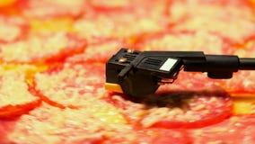 Salchichones de la pizza que hacen girar en jugador del vinilo de la placa giratoria Concepto de partido, comida basura deliciosa almacen de metraje de vídeo