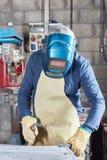 Saldatore che usando vestiario di protezione e casco fotografia stock