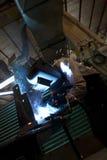 Saldatore dell'arco con le scintille della saldatura. Immagini Stock