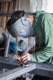 Saldatore industriale che funziona un metallo di saldatura con la maschera protettiva Fotografia Stock