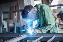 Saldatore industriale che funziona un metallo di saldatura con la maschera protettiva Fotografia Stock Libera da Diritti