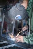 Saldatore industriale che funziona un metallo di saldatura con la maschera protettiva Immagini Stock Libere da Diritti