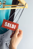 Saldi tags. Sale, elegant clothes with tags bid, with hand royalty free stock photo