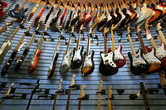 For Sale. Guitars on the wall awaiting for sale Stock Photos