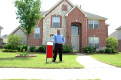 For Sale. House for sale. Man outside could be a realtor agent, buyer, seller. Sign is left blank for your own text stock photo