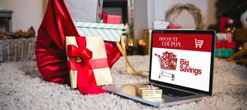 Composite image of sale advertisement. Sale advertisement against gift sack, gift and laptop placed together on rug Royalty Free Stock Photo