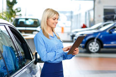 Sale assistant showing the car. Involved in work. Pleasant smiling beautiful female  sale assistant holding tablet and standing near car while doing her job Royalty Free Stock Photo