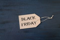 Sale banner with text word Black Friday on cardboard label on dark background stock photography