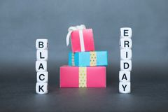 Sale banner with text word Black Friday and multicolored gift boxes royalty free stock photos