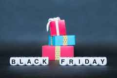 Sale banner with text word Black Friday and multicolored gift boxes stock images
