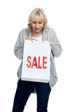 Sale bargains. Casual woman looking in her shopping bag with SALE sign on it in studio Royalty Free Stock Images