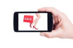 Sale begrepp för röda kvinnaskor på telefonskärm Royaltyfria Bilder