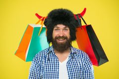 Sale, big savings no waiting. Bearded man smiling with purchases bought at sale. Happy hipster in bull horns hat holding. Shopping bags after seasonal sale royalty free stock photography
