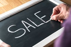 Sale blackboard banner in store, shop or marketplace to promote bargain prices or clearance. Small business owner, salesman. Sale blackboard banner in store royalty free stock photos