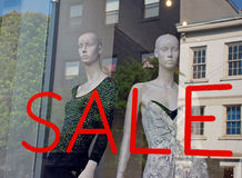Sale Boutique Window Mannequins. Two models in the front of a luxury fashion store. Found in a main street historic district.  Some of the buildings reflect in Royalty Free Stock Photography