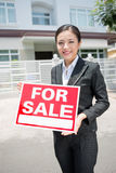 Sale business. Vertical portrait of a young realtor standing with a placard in hands Royalty Free Stock Photography