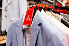 Sale in the  casual menswear store. Sale in the  business  menswear store. Red sign of  the sale on rack with men's suits in the interior of the shop Royalty Free Stock Photo