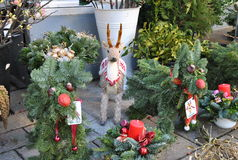 Sale of Christmas decorations on the street market. Street market in Vienna: Toy deer surrounded by elegantly decorated Christmas trees Royalty Free Stock Photos