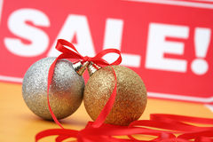 Sale of Christmas spheres. Sale. Christmas. New Year's spheres lie on a yellow background with a red tape Royalty Free Stock Photography