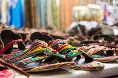 Sale of colored sandals at the african shop. On blur background Stock Photos