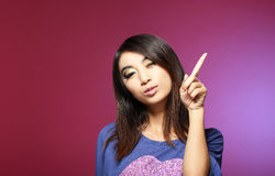 Sale Concept. Friendly Young Saleswoman Pointing with Her Index Finger Upwards Stock Photo
