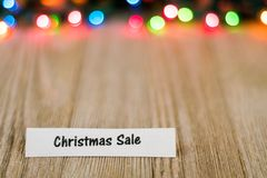 Christmas Sale Concept on wooden board and colored lights, selective focus, room for copy stock photo