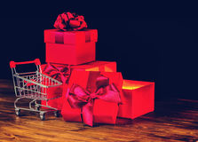 Sale concert, presents, holiday greeting card with festive opene. D boxes with bow and shopping cart on wooden background, close up Royalty Free Stock Photo