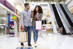 Sale And Consumerism Concept. Happy Couple Walking In Mall. Sale And Consumerism Concept. Happy Couple Walking In Shopping Mall royalty free stock photography