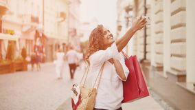 Sale, consumerism: Confident lady with shopping bags make selfie on smartphone. Sunshine background.  stock video